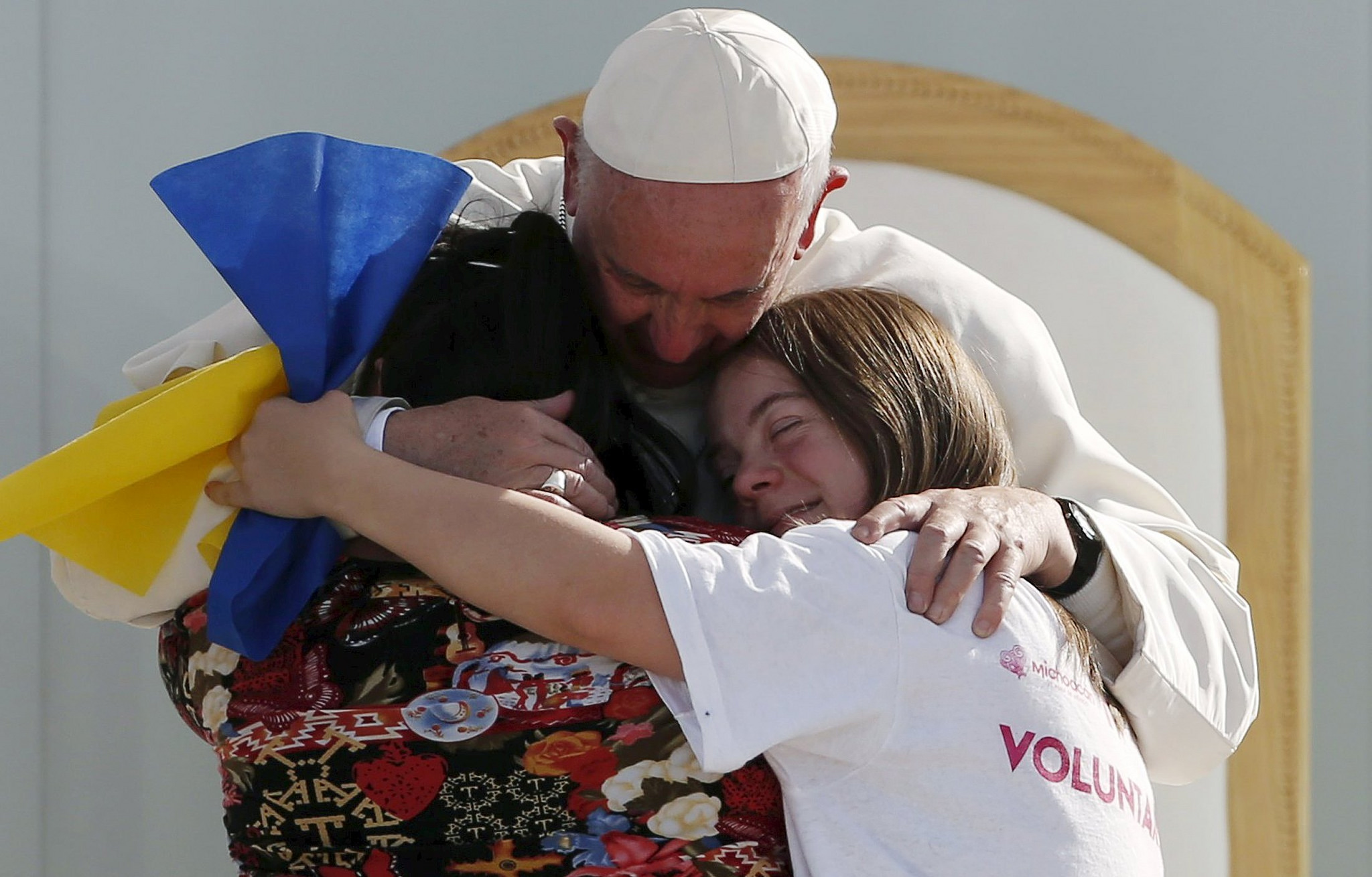 Pope Francis hugging two girls during Youth Days in Krakow.